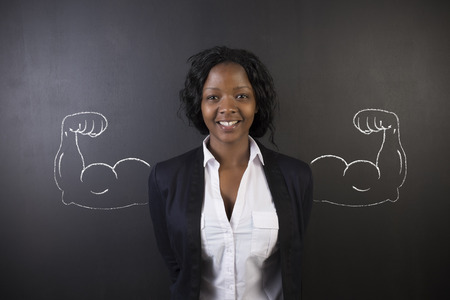 strong arm: South African or African American woman teacher with healthy strong chalk arm muscles for success on blackboard background