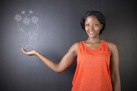 growing flowers: South African or African American woman teacher or student standing against a blackboard background holding chalk growing flowers