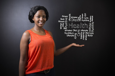 South African or African American woman teacher or student standing with her hand out against a blackboard background with a chalk health diagram