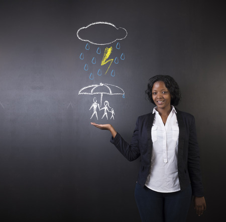 insurance protection: South African or African American woman teacher or student holding out her hand, displaying an insurance concept while thinking about protecting family from natural disaster on a blackboard background