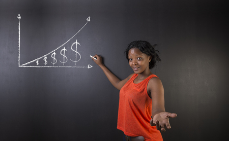 african student: South African or African American woman teacher or student against blackboard background showing chalk money graph
