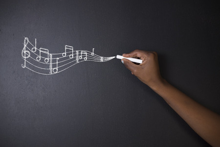 Learn music South African or African American teacher or student writing chalk music notes on blackboard background