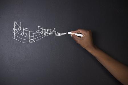 Naučte hudbu Jihoafrický nebo africký Američan učitelů nebo student psaní křídou hudební poznámky na tabuli pozadí