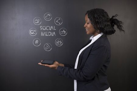 business woman tablet: South African or African American woman teacher or student holding tablet computer showing social media chalk concept on a blackboard background
