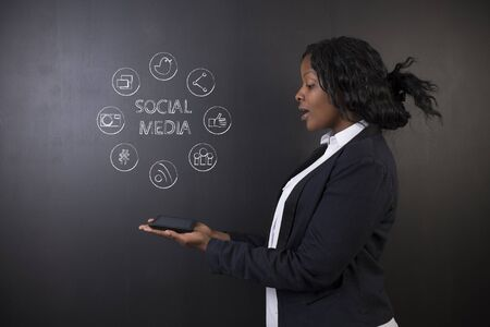 african teacher: South African or African American woman teacher or student excited holding a tablet computer against a blackboard background with a social media chalk concept Stock Photo