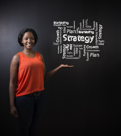 South African or African American woman teacher or student with her hand out standing against a blackboard background with a chalk strategy diagram photo