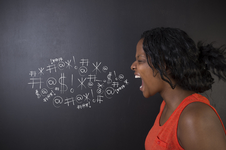 standing against: South African or African American woman teacher or student standing against a blackboard background swearing chalk words bubble Stock Photo