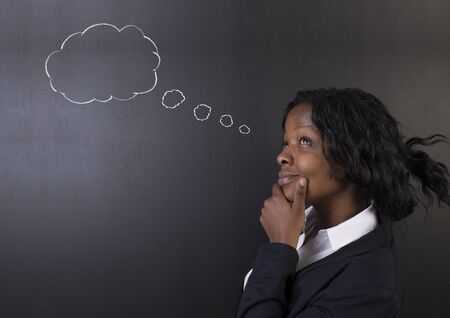 thought clouds: South African or African American woman teacher or student thinking with chalk thought clouds