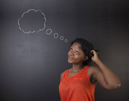 thought clouds: South African or African American woman teacher or student thinking, scratching her head standing against a blackboard background with chalk thought clouds