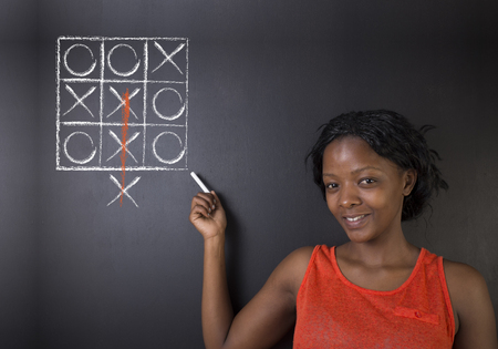 think out of the box: Thinking out of the box South African or African American woman teacher or student pointing at a tic tac toe concept on a blackboard background Stock Photo