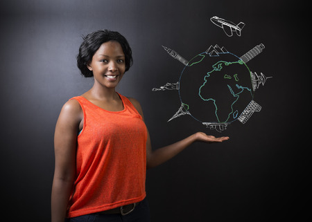 South African or African American woman teacher or student holding chalk globe and jet world travel on a blackboard background Foto de archivo