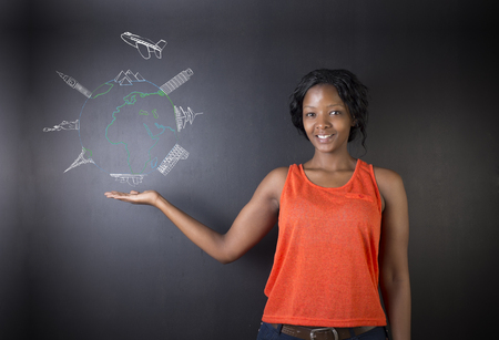 South African or African American woman teacher or student holding her hand out displaying chalk globe and jet world travel on a blackboard background