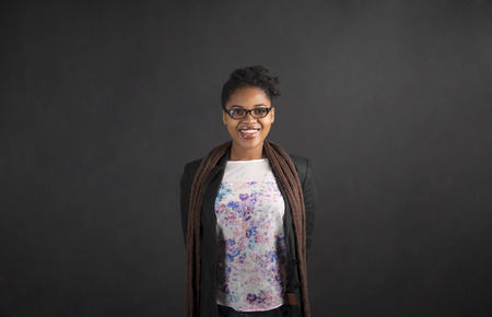 BLACK GIRL: South African or African American black woman teacher or student with her arms behind her back on chalk black board background inside Stock Photo