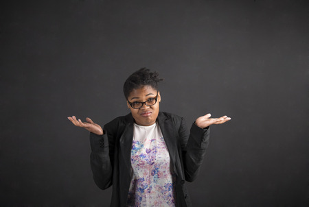 adult student: South African or African American black woman teacher or student posing with an I dont know gesture on a chalk blackboard background inside