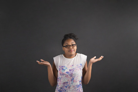 i don't know: South African or African American black woman teacher or student posing with an I dont know gesture on a chalk blackboard background inside
