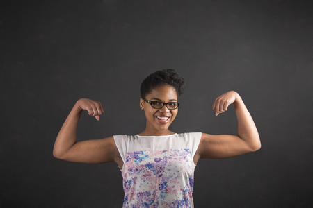 strong woman: South African or African American black woman teacher or student with strong muscular arms standing against a chalk blackboard background inside Stock Photo
