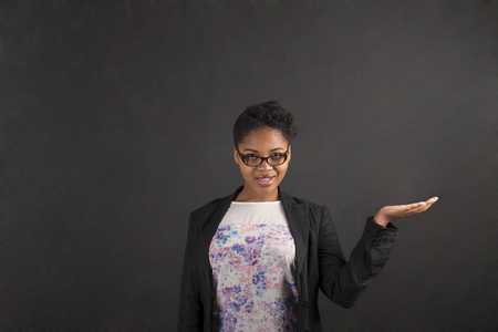 black board: South African or African American black woman teacher or student holding her hand out to the side standing against a chalk blackboard background inside Stock Photo