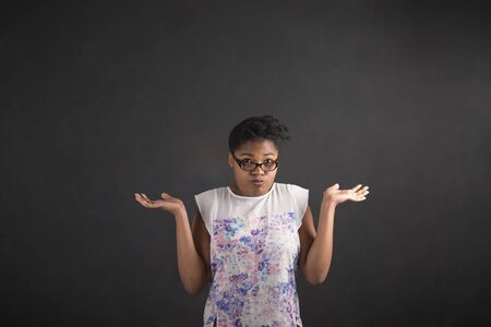i dont know: South African or African American black woman teacher or student posing with an I dont know gesture on a chalk blackboard background inside