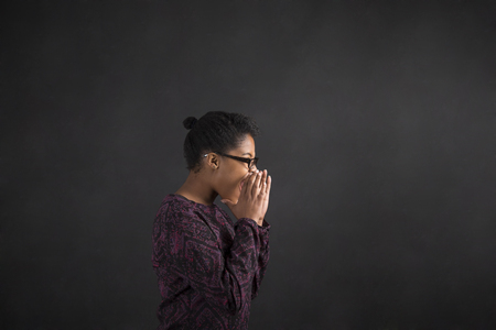angry hand: South African or African American black woman teacher or student shouting or screaming standing against a chalk blackboard background inside