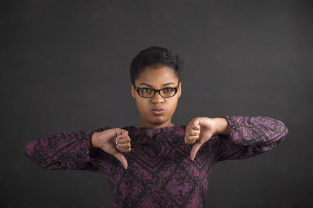 hand signal: South African or African American black woman teacher or student with thumbs down hand signal on a chalk black board background inside