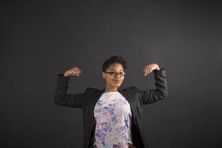 negras africanas: Profesor sudafricano o afroamericano negro mujer o estudiante con fuertes brazos musculosos de pie contra un fondo de la pizarra de tiza en el interior