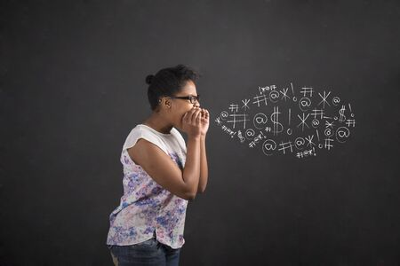 swearing: South African or African American black woman teacher or student shouting, screaming or swearing standing against a chalk blackboard background inside Stock Photo