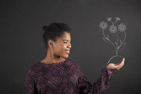 chalk drawing: South African or African American black woman teacher or student holding a growing flower in her hand standing against a chalk blackboard background inside