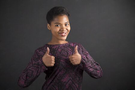 teach: South African or African American black woman teacher or student with a thumbs up hand signal standing against a chalk blackboard background inside