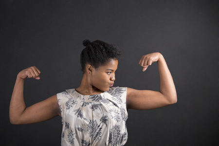woman muscle: South African or African American black woman teacher or student with strong muscular arms standing against a chalk blackboard background inside Stock Photo