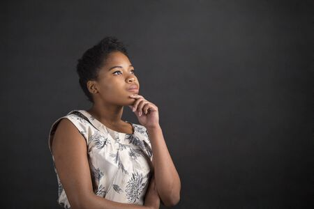 teach: South African or African American black woman teacher or student with her hand on her chin whilst thinking standing against a chalk blackboard background inside