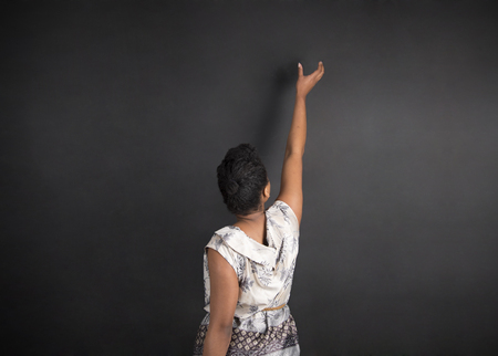 reaching up: South African or African American woman teacher or student with hand reaching up on chalk black board background inside