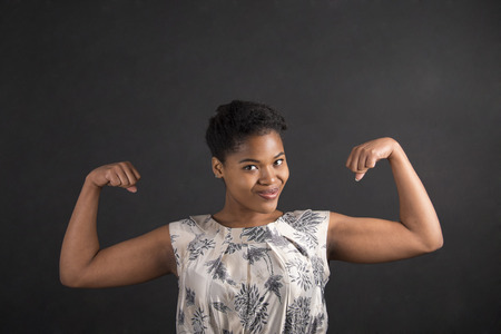 strong: South African or African American black woman teacher or student with strong muscular arms standing against a chalk blackboard background inside Stock Photo