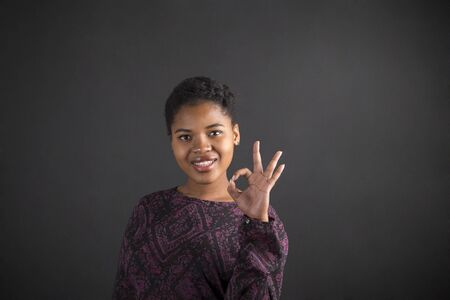 student study: South African or African American black woman teacher or student holding up a perfect hand signal on a chalk blackboard background inside Stock Photo