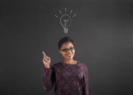 South African or African American black woman teacher or student with a good idea or answer lighbulb standing against a chalk blackboard background inside