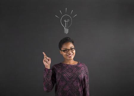 idée: Professeur sud-africain ou afro-américaine femme noire ou de l'étudiant avec une bonne idée ou repondre lighbulb debout contre un fond craie de tableau noir à l'intérieur Banque d'images