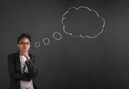 Professeur sud-africain ou afro-américaine femme noire ou un étudiant avec sa main sur son menton en pensant nuage de pensée ou une bulle debout contre un fond craie de tableau noir à l'intérieur