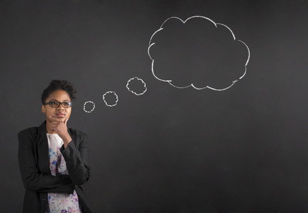 thought clouds: South African or African American black woman teacher or student with her hand on her chin whilst thinking thought cloud or bubble standing against a chalk blackboard background inside Stock Photo