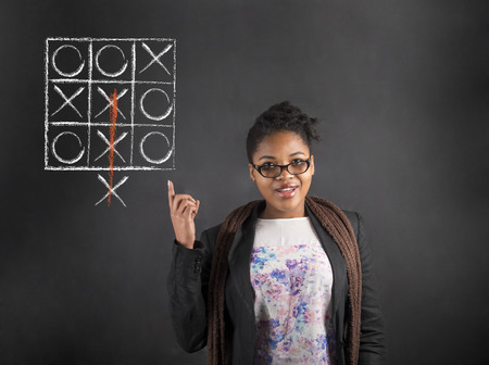 thinking out of the box: South African or African American black woman teacher or student with a good idea or answer with tic tac toe thinking out the box diagram standing against a chalk blackboard background inside