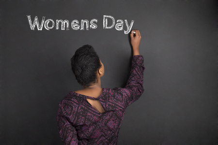 young womens: South African or African American woman teacher writing Womens Day on chalk black board background inside