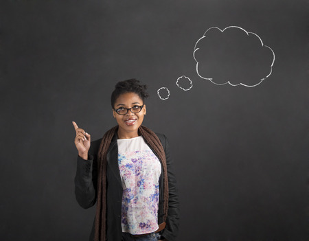 answer: South African or African American black woman teacher or student with a good idea or answer thought or speech clouds standing against a chalk blackboard background inside