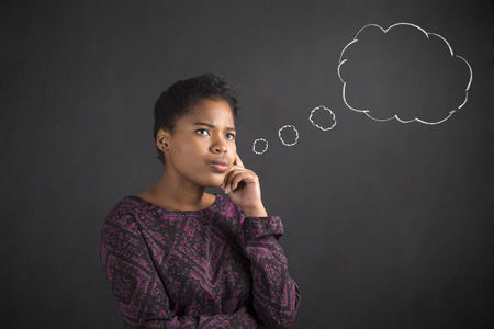 thought clouds: South African or African American black woman teacher or student with her hand on her chin whilst thinking thought clouds standing against a chalk blackboard background inside