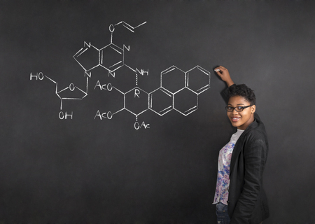 South African or African American woman teacher writing science on chalk black board background Standard-Bild