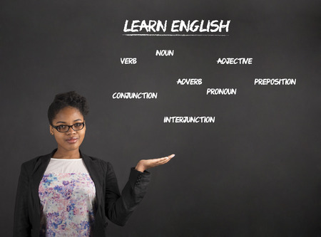 african student: South African or African American black woman teacher or student holding her hand out to the side showing learn English standing against a chalk blackboard background inside