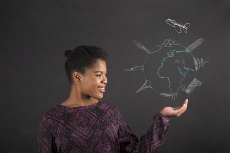 South African or African American black woman teacher or student holding her hand out to the side with a global travel diagram standing against a chalk blackboard background inside
