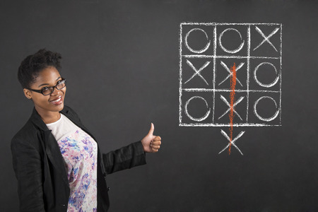 South African or African American black woman teacher or student with a thumbs up hand signal with tic tac toe standing against a chalk blackboard background inside