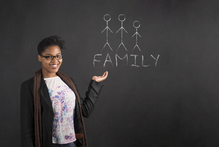 South African or African American black woman teacher or student holding her hand out to the side with a family diagram standing against a chalk blackboard background inside