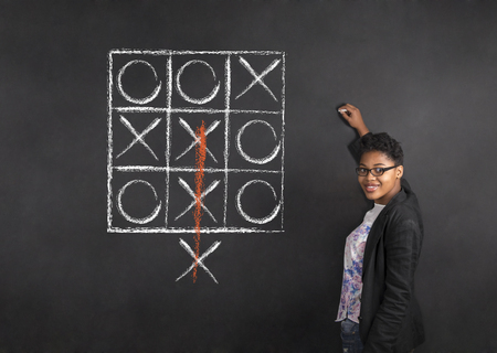tic tac toe: South African or African American woman teacher writing tic tac toe on chalk black board background Stock Photo