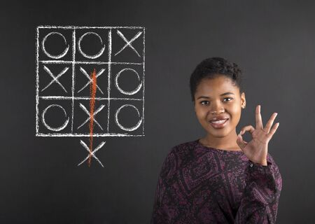 tic tac toe: South African or African American black woman teacher or student holding up a perfect hand signal with a tic tac toe diagram on a chalk blackboard background inside