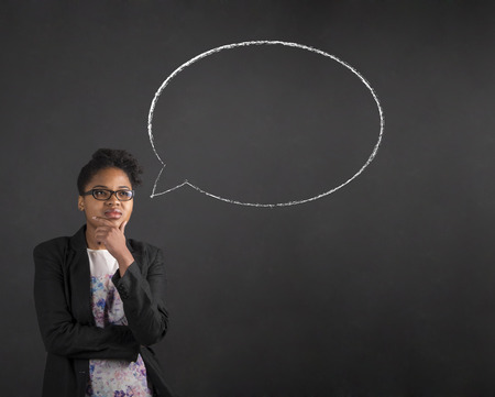 South African or African American black woman teacher or student with her hand on her chin whilst thinking thought bubble standing against a chalk black board background inside Standard-Bild