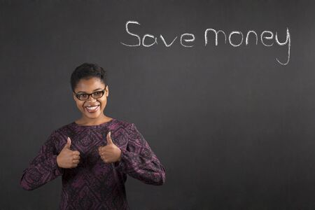 american money: South African or African American black woman teacher or student with a thumbs up hand signal to saving money standing against a chalk blackboard background inside
